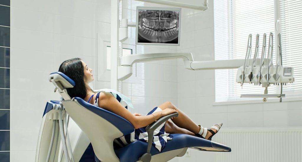 Patient sitting on dental chair wearing dental bib