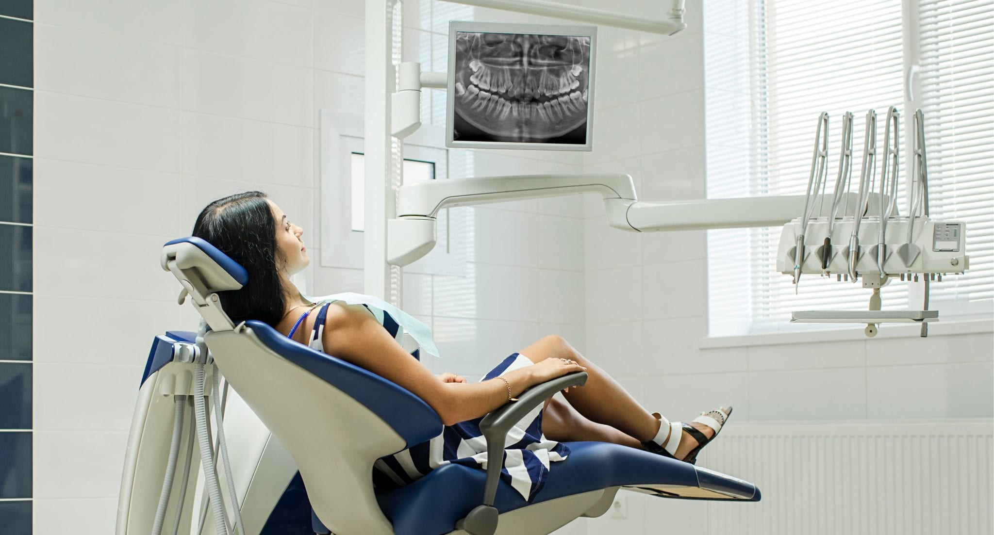 Patient sitting on dental chair wearing dental bib