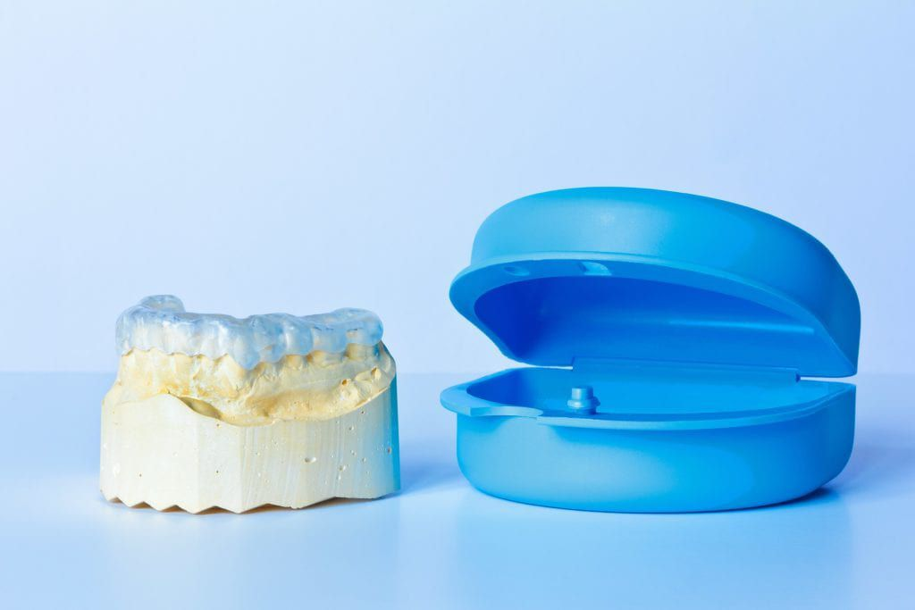 Mouth guard on a teeth mold next to a protective case