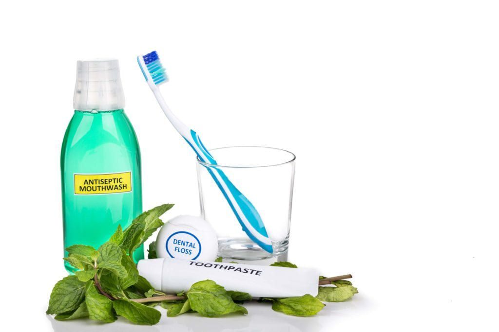 Mouthwash, floss, toothbrush, and toothpaste surrounded by mint leaves