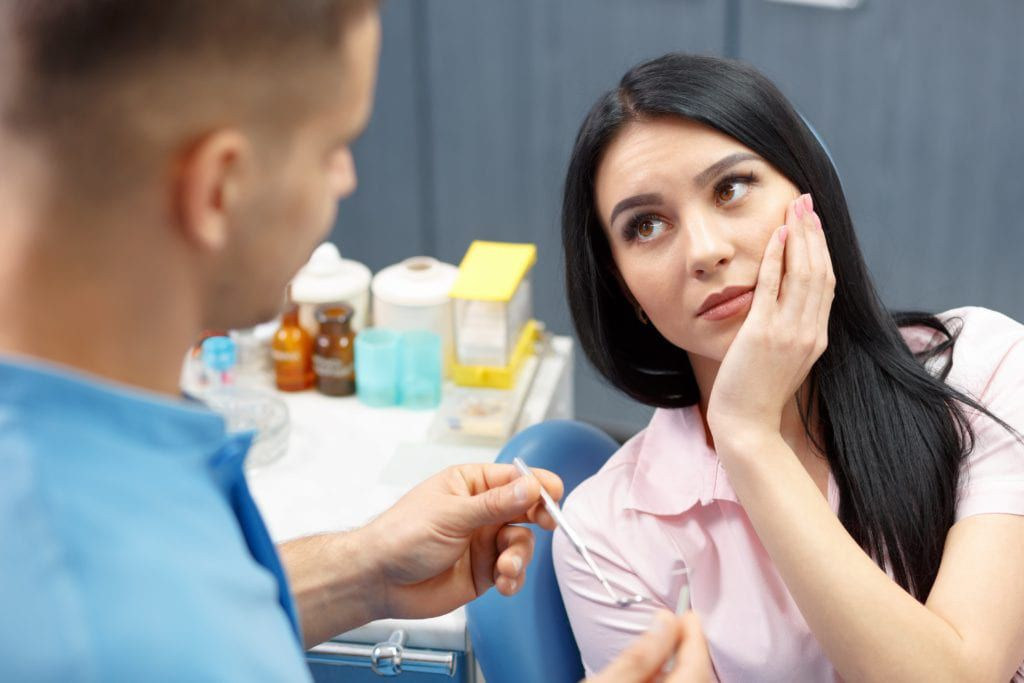 Woman with tooth pain having a dental exam